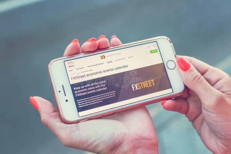 MOSCOU, RÚSSIA - 4 DE JUNHO DE 2019: Web site da empresa financeira de Alpari no smartphone nas mãos da mulher foto de stock