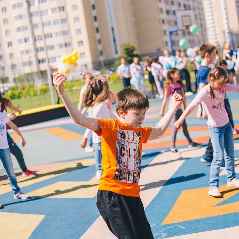 Moscou, Rússia - 22 de maio de 2019: Crianças que dançam na escola em um feriado no recreio Foco no menino foto de stock royalty free