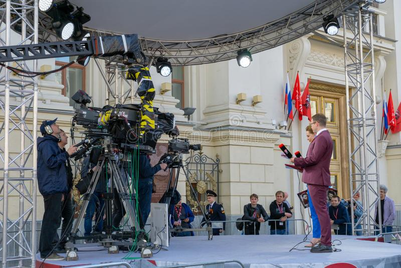 MOSCOU, RÚSSIA - 9 DE MAIO DE 2019: Gravando programa de TV durante a Parada do Dia da Vitória Jornalistas do canal TVC foto de stock royalty free