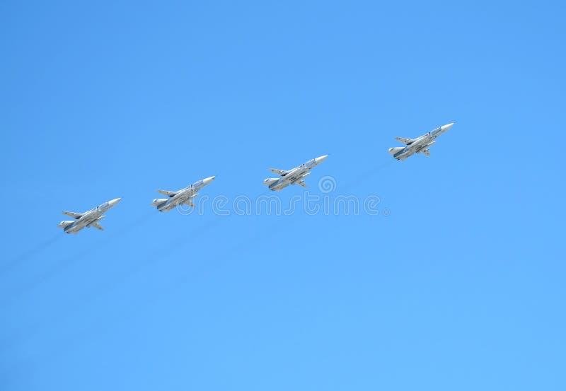 MOSCOU, RÚSSIA - 9 de maio de 2018: Grupo dos bombardeiros linhas da frente táticos militares SU-24 do russo em voo no céu azul fotografia de stock