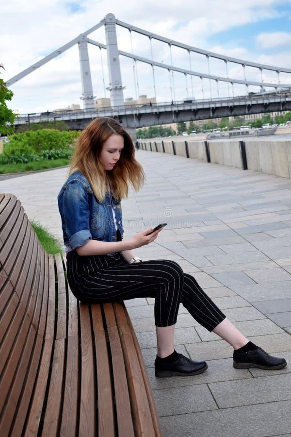 Moscou, Rússia - 13 de maio de 2019: A jovem mulher está olhando em seu smartphone na terraplenagem de Krymskaya fotos de stock royalty free