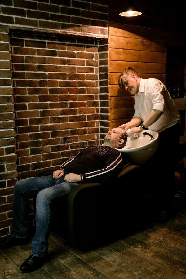 MOSCOU, RÚSSIA - 24 DE MAIO DE 2018: Lavagem de Sergei Urazov do barbeiro do russo foto de stock royalty free
