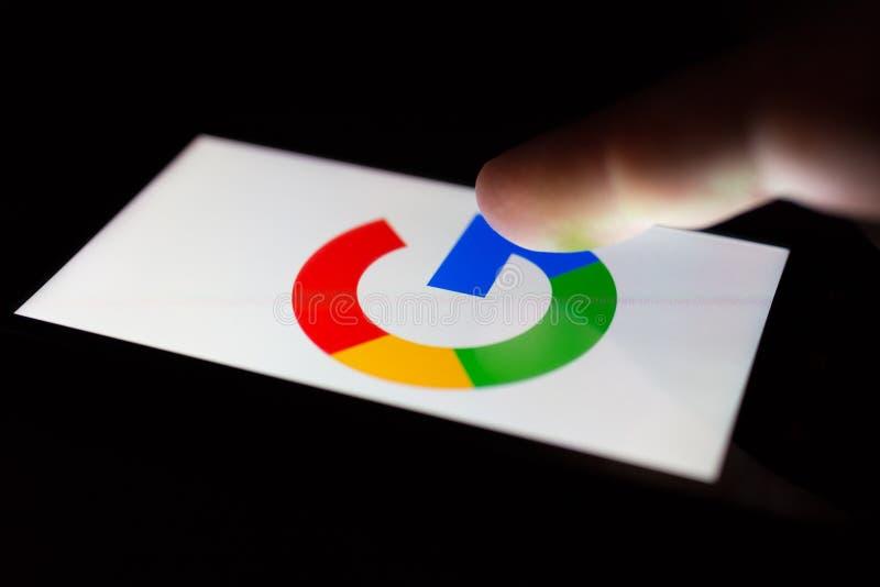 MOSCOU, RÚSSIA - 9 de maio de 2018: Um smartphone que encontra-se em uma tabela no escuro, indicando o logotipo de Google foto de stock