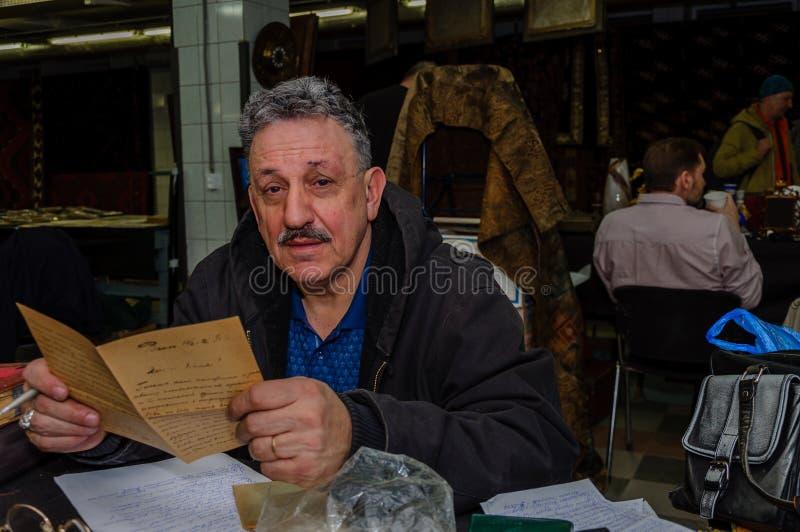 Moscou, Rússia - 19 de março de 2017: O antiquário grisalho lê um manuscrito antigo em antecipação aos compradores foto de stock royalty free