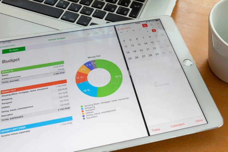 Moscou/Rússia - 2 de março de 2019: O ipad branco encontra-se no teclado do macbook, na tela do diagrama Está próximo um copo imagem de stock royalty free