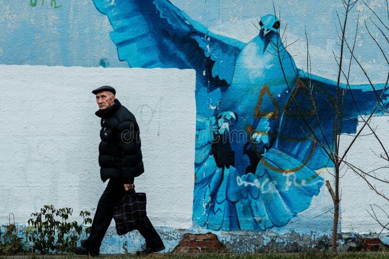 MOSCOU, RÚSSIA - 11 DE NOVEMBRO DE 2019: Avô caminha pela parede com uma pomba fotos de stock