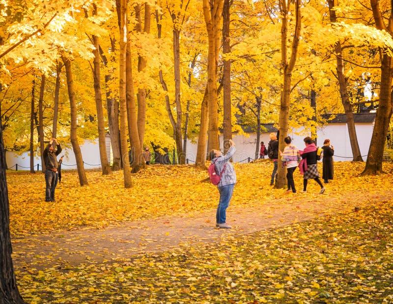 Moscou, Rússia - 11 de outubro de 2018: Os turistas andam o parque do outono Os povos tomam imagens no fundo de um bonito fotos de stock