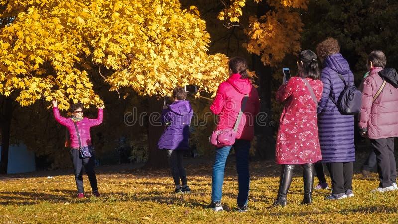 Moscou, Rússia - 11 de outubro de 2018: Os turistas chineses andam o parque do outono Os povos asiáticos tomam imagens no fundo d foto de stock