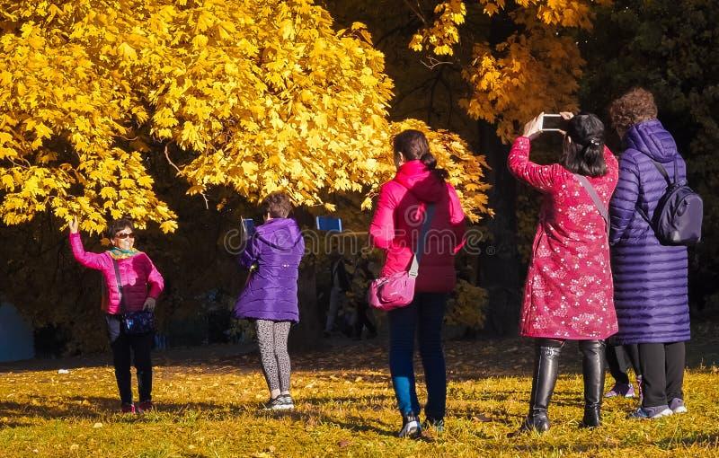 Moscou, Rússia - 11 de outubro de 2018: Os turistas chineses andam o parque do outono Os povos asiáticos tomam imagens no fundo d fotografia de stock royalty free