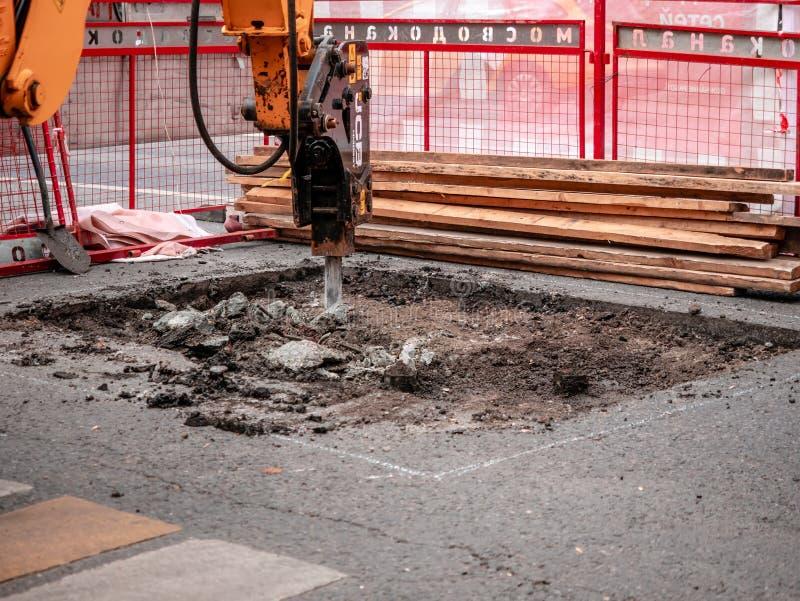 Moscou, Rússia - 14 de setembro de 2019: Uma escavadora com chisel hidráulico remove o pavimento asfalto Carriageway Trabalhos de imagens de stock