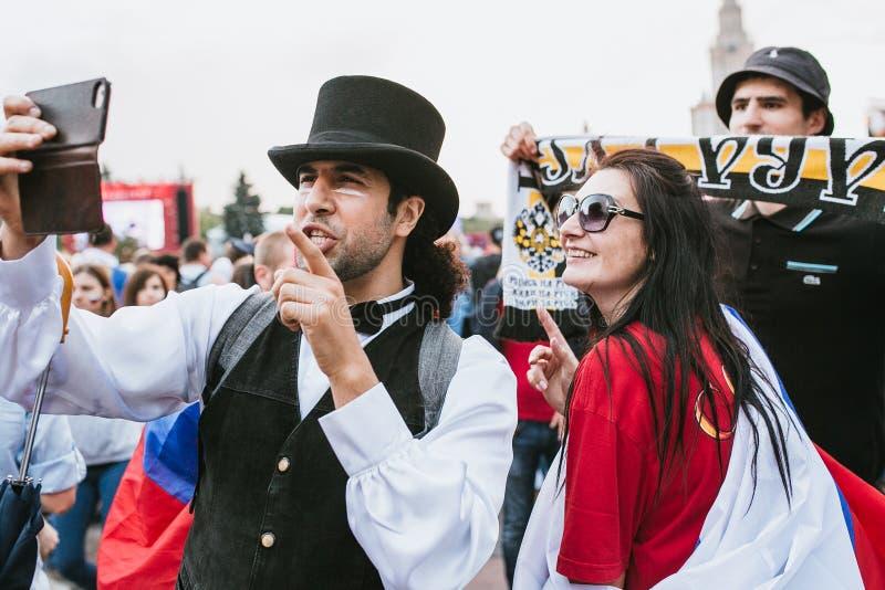 MOSCOU, RÚSSIA - EM JULHO DE 2018: Um homem em um chapéu de jogador, no laço e em um terno fotografou a zona do fã da mulher dura fotografia de stock royalty free