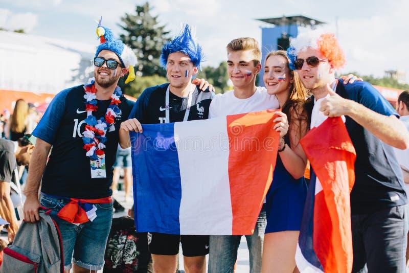 MOSCOU, RÚSSIA - EM JUNHO DE 2018: Um grupo de fãs franceses com bandeiras nacionais e as perucas são fotografados com um indivíd fotografia de stock royalty free