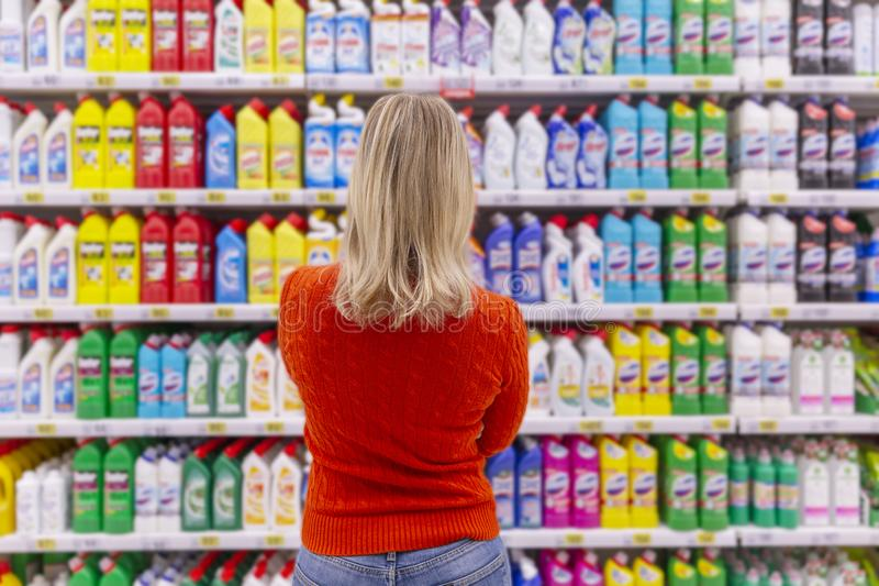 Moscou, Rússia, 11/22/2018 A jovem mulher na loja escolhe o produto de limpeza, vista da parte traseira imagem de stock royalty free