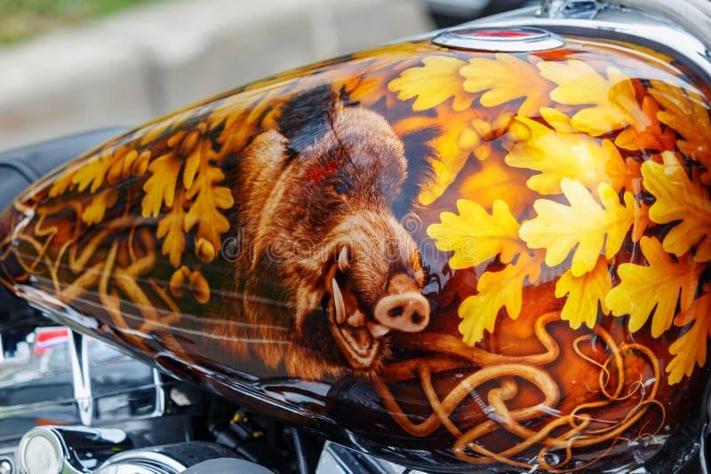 Moscou, R?ssia - 4 de maio de 2019: Motocicleta de Harley Davidson com airbrushing do javali nas folhas do carvalho no close up d fotografia de stock royalty free
