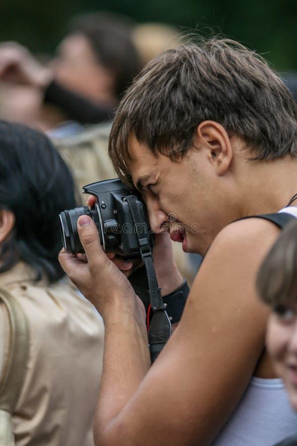 2010 08 22, Moscou, R?ssia Uma câmera da foto da terra arrendada do homem e um pessoa de tiro imagem de stock