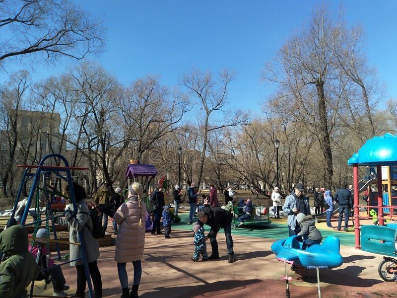 Moscou, RF-março, 31: os pais andam com suas crianças no campo de jogos no parque da cidade na mola adiantada foto de stock royalty free