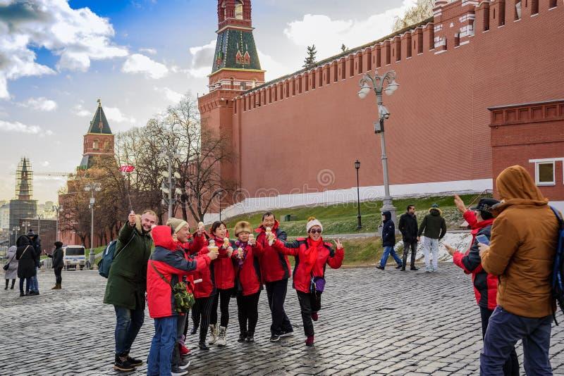 Moscou, Russie Grand dos rouge Des touristes et les voyageurs joyeux sont photographiés pour la mémoire images libres de droits