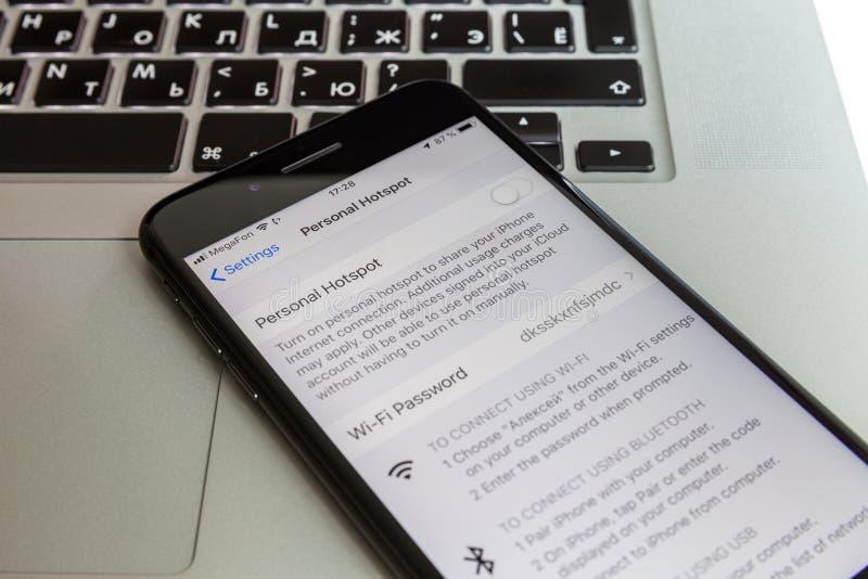 Moscou/Russie - 10 juillet 2019 : IPhone 8 noir plus des repos sur le clavier de MacBook Le modem est arrêté sur l'écran photo stock