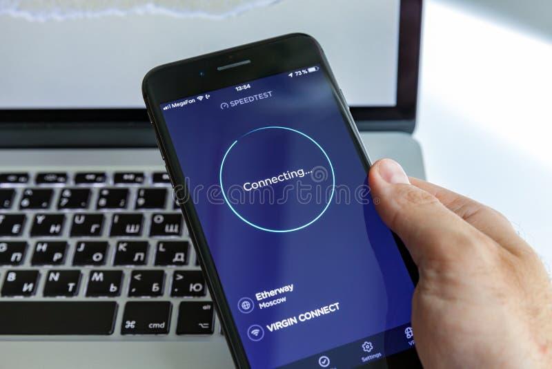 Moscou/Russie - 13 juillet 2019 : Plus noir d'iPhone 8 à disposition sur le fond de MacBook Programme à l'écran SpeedTest photo libre de droits
