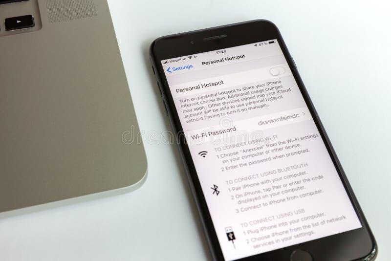 Moscou/Russie - 10 juillet 2019 : Plus noir et MacBook d'iPhone 8 Le modem est arrêté sur l'écran image libre de droits