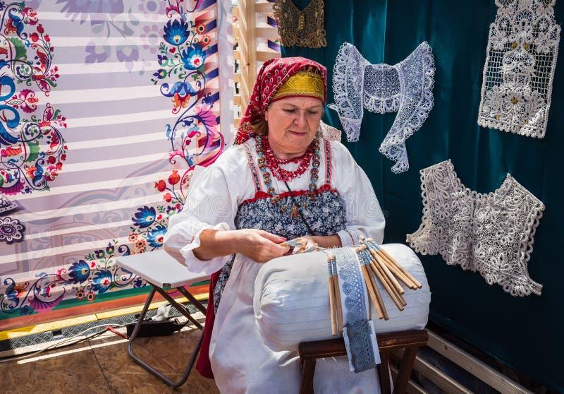 Moscou, Victory Park, le 11 juin 2018 : Une femme agée dans le costume national russe occupé dans le métier traditionnel images stock