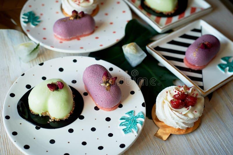 Moscovie backt Purpurrotes und zitronengelbes zusammen Pistazie und Frucht Meringe Anna Pavlova Kulinarische Kunst Auf gestreifte stockbilder