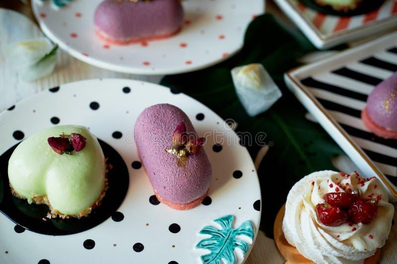 Moscovie backt Purpurrotes und zitronengelbes zusammen Pistazie und Frucht Meringe Anna Pavlova Kulinarische Kunst Auf gestreifte lizenzfreies stockbild
