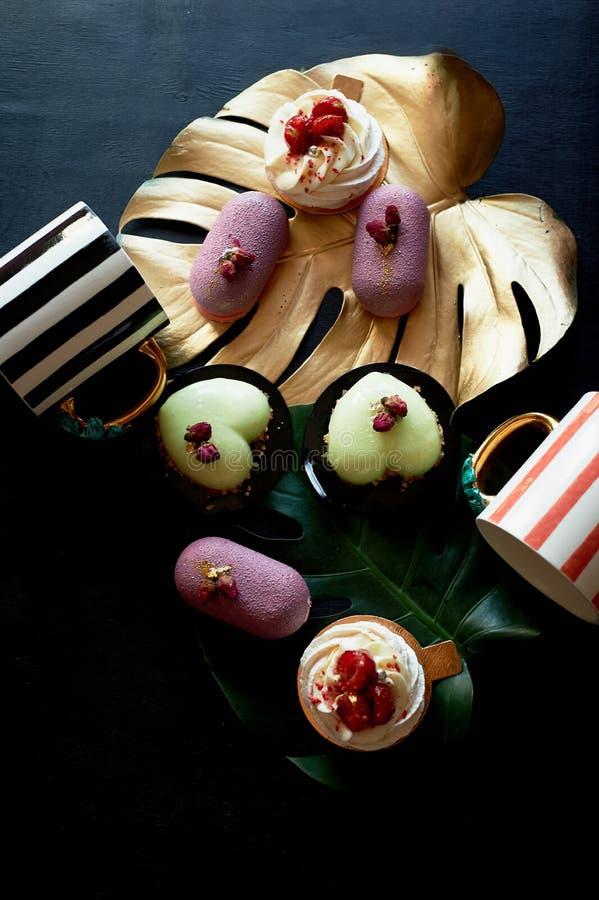 Moscovie backt Purpurrotes und zitronengelbes zusammen Pistazie und Frucht Meringe Anna Pavlova Kulinarische Kunst Goldblatt mons stockbild