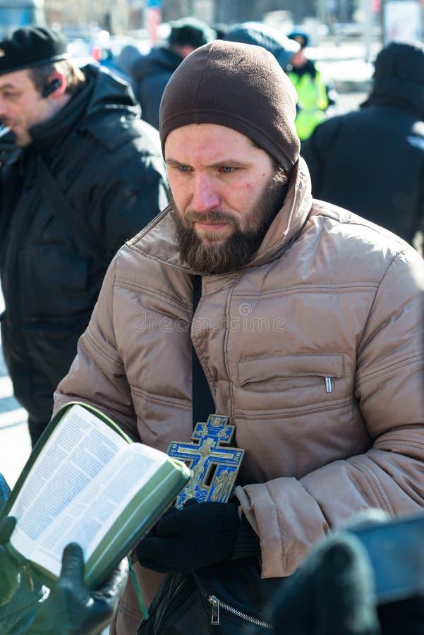Os activistas ortodoxos leram a Bíblia alto no piquete para livrar o motim do bichano fotografia de stock