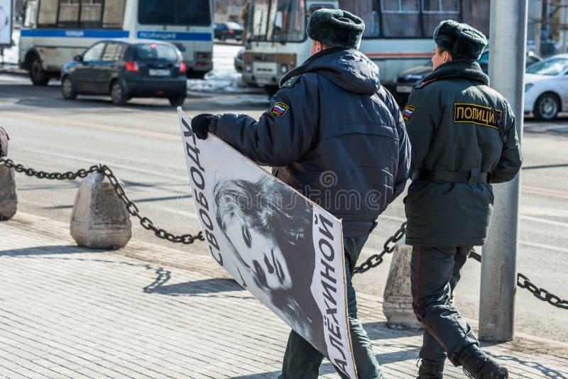 A polícia traz o cartaz confiscado do activista imagens de stock