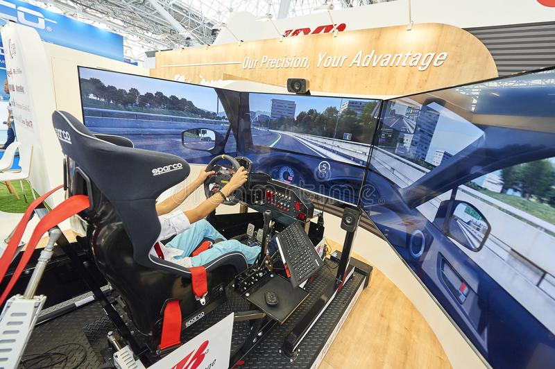 MOSCOW, AUG. 22, 2017: View on exhibition stand with 3d car driving simulator with wide led screens, electronic hydraulic tilting royalty free stock photography
