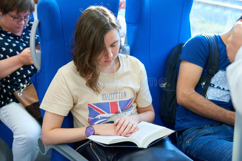 MOSCOW, AUG.29, 2018: View on the girl reading a book and other seating people in passenger train saloon on new Moscow Ring Railwa stock photo