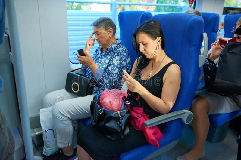 MOSCOW, AUG.29, 2018: View on seating people in the passenger train saloon on new Moscow Ring Railway line. Woman is crocheting. P stock image