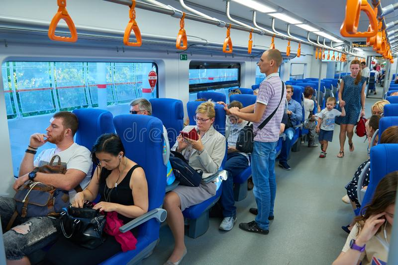 MOSCOW, AUG.29, 2018: View on seating, standing and walking people in the passenger train saloon on Moscow Ring Railway line. City stock photography