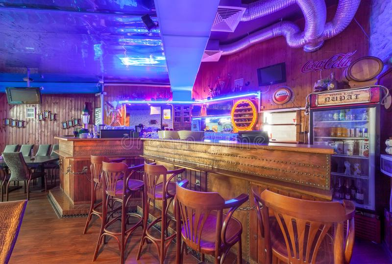 MOSCOW - AUGUST 2014: Interior of the night club. `PIRAT`. Bar counter in ship style with neon lights and bar stools stock images