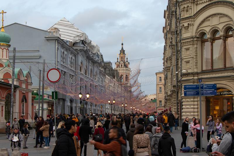 Moscow City Street. A lot of people walking around the city square, Glowing lights of garland hang above the street. stock photography