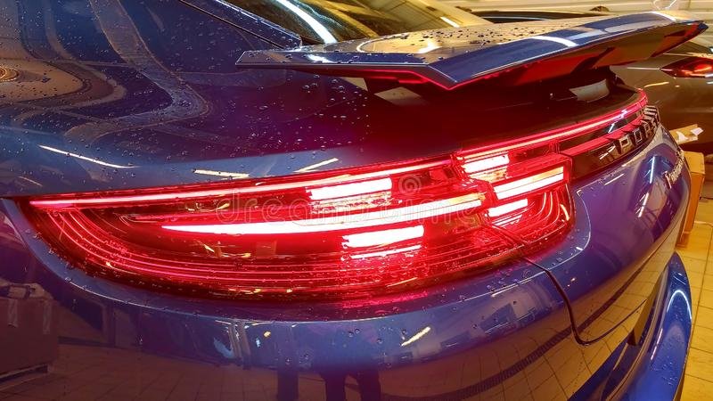 Moscow. February 2019. Rear taillights of new blue Porsche Panamera Turbo with adaptive rear aerodynamic spoiler. Rain drops stock photo
