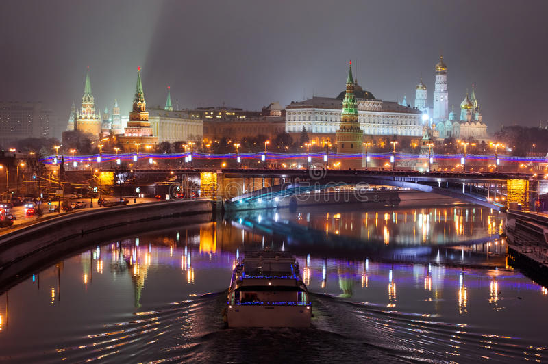 Moscow Kremlin night lights. Moscow Kremlin at vague winter night. Moscow-river and tourist pleasure boat. View from bridge stock images