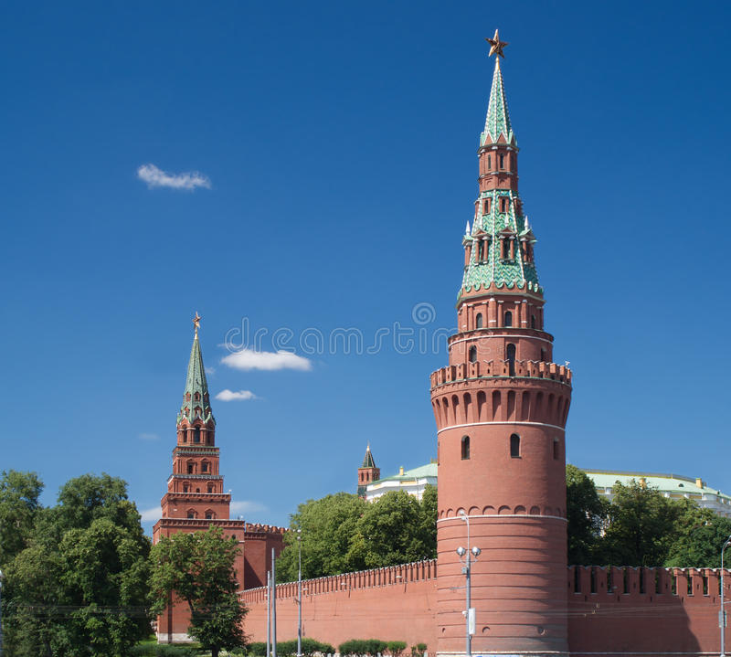 Moscow Kremlin towers in summer day. Moscow Kremlin wall with Vodovzvodnaya and Borovitskaya towers in summer day stock images