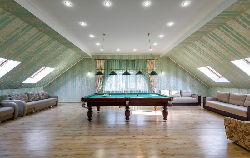 Large hall with couches and pool table. Moscow - May 2, 2018: Modern interior of residential house or hotel. Large hall with couches and pool table. Interior of stock images