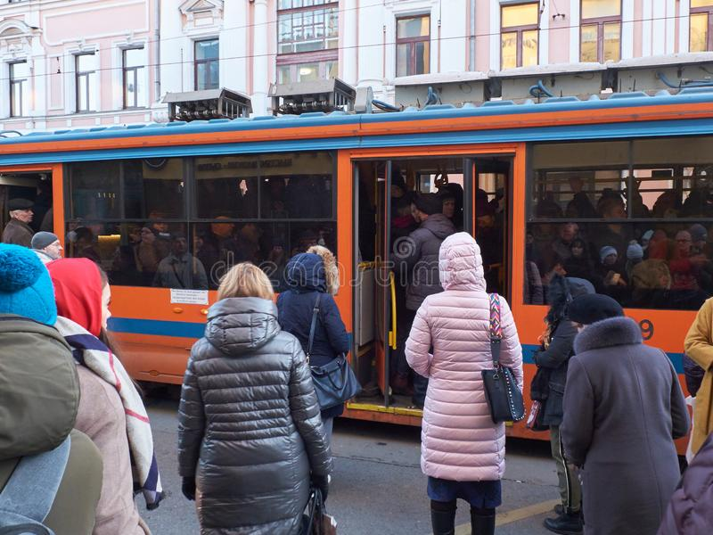 MOSCOW, NOV. 13, 2018: View on modern tramway and a lot of people trying to get in. Morning hard heavy traffic and people in the q royalty free stock photos