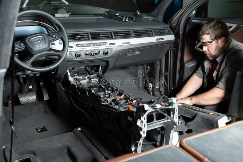 Moscow. November 2018. A mechanic repairs an Audi SUV Repairing wiring, gearboxes, disassembled interior premium crossover. Removed chairs. Leather interior stock images