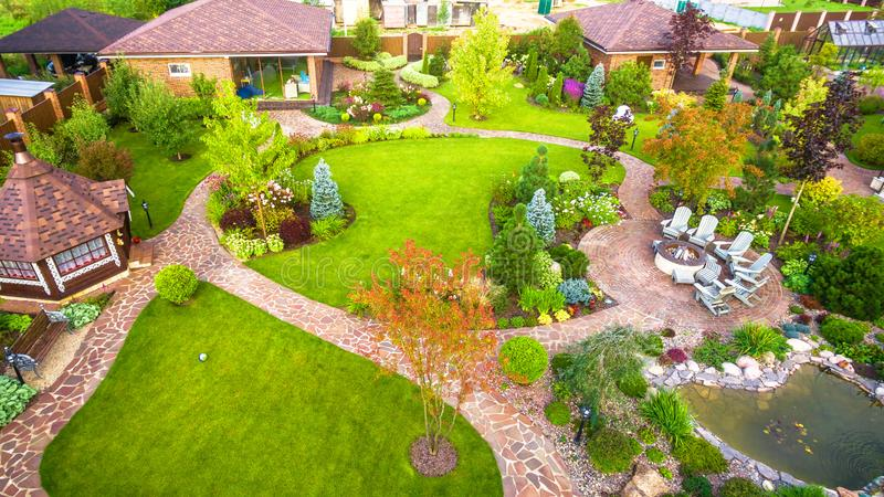 Landscape design at residential house taken from above. Beautiful landscaping in home garden in summer. Moscow Region - Aug 24, 2019: Landscape design at royalty free stock image