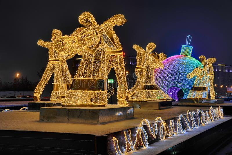 Illuminated Dancing Couples and Christmas Tree Ball on Poklonnaya Hill. MOSCOW, RUSSIA - The amazing luminous sculptures in form of dancing couples in the stock photos