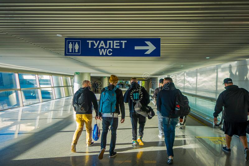 MOSCOW, RUSSIA- APRIL, 24, 2018: Indoor view of unidentified people walking under a informative sign of toilets at right royalty free stock image