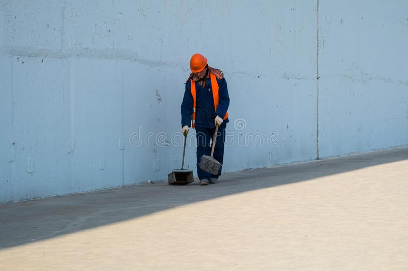 MOSCOW, RUSSIA,APRIL,29.2019:Janitor in a special uniform removes debris, dirt and dust from the city sidewalk.  stock images