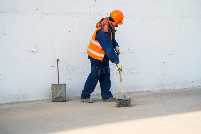 MOSCOW, RUSSIA,APRIL,29.2019:Janitor in a special uniform removes debris, dirt and dust from the city sidewalk.  royalty free stock photo
