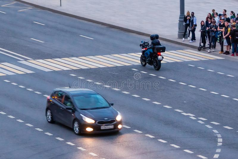 MOSCOW, RUSSIA - APRIL 30, 2018: A motorcyclist rides a pedestrian zebra crossing. Top view from Bolshoy Moskvoretsky Bridge. stock photos