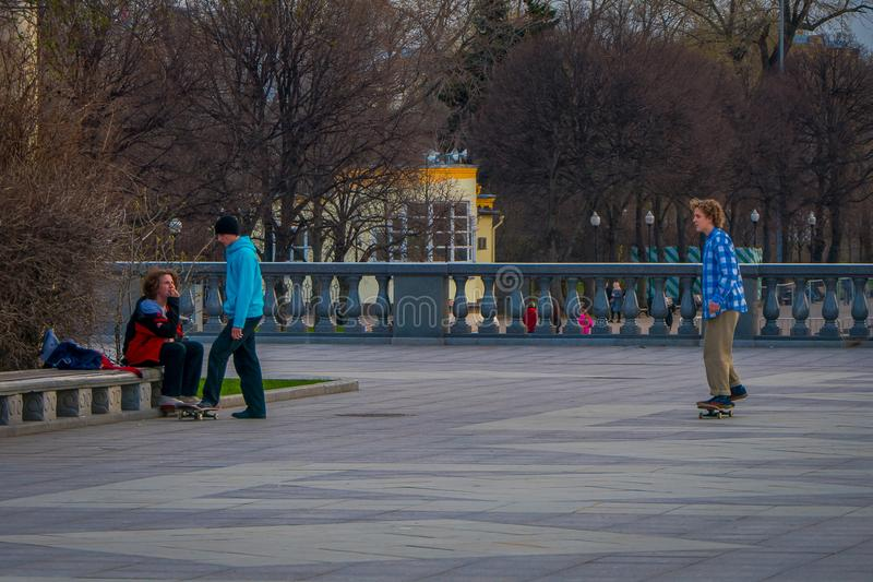 MOSCOW, RUSSIA- APRIL, 24, 2018: Outdoor view of teenagers practicing roller skating in a park without protection,in a. Gorky park during a sunny day in Moscow royalty free stock image