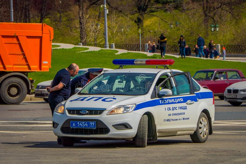 MOSCOW, RUSSIA- APRIL, 24, 2018: Outdoor view of unidentified man inside of a police car driving on Red Square in a stock image